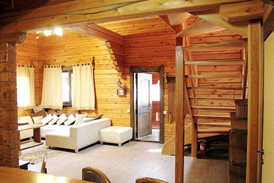 Гостиная с камином в коттедже отеля Мелодия гор
