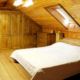 Одна из спален в коттедже отеля Мелодия гор