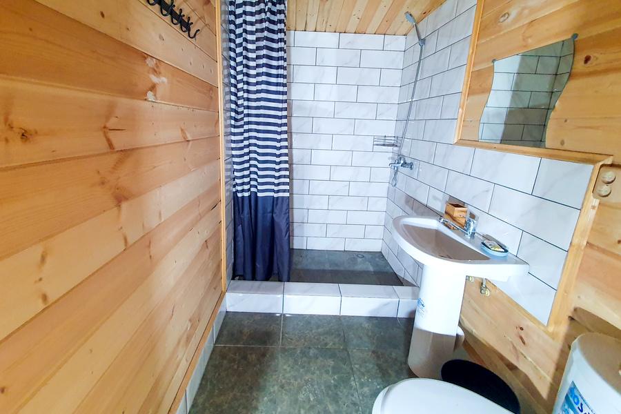 Туалетная комната в деревянном коттедже на территории парк-отеля У монастыря